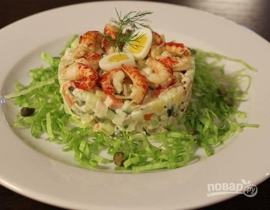 Листья салата нарежем соломкой. Выкладываем салат с помощью кулинарного кольца, вокруг него — измельченные листья салата. Украшаем салат раковыми шейками и перепелиным яйцом.