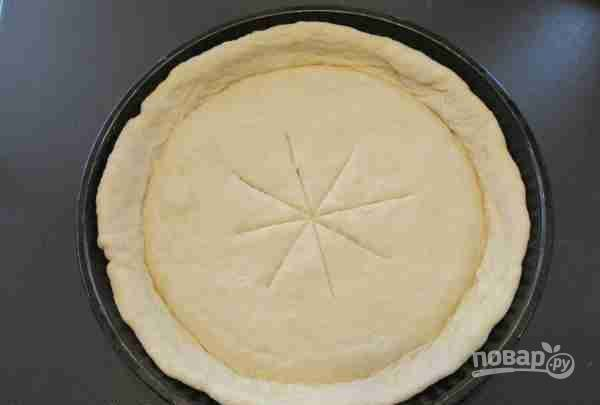 5.Форму для пиццы смажьте маслом, уложите на дно раскатанное в круг тесто, сделайте бортики. Отступив 10 см от бортиков, сделайте в центре крестообразные надрезы.