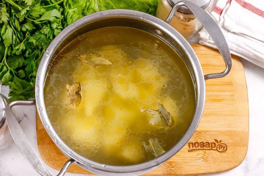 Картофель очистите от кожуры и нарежьте средними кубиками. Выложите нарезку в кастрюлю и влейте куриный бульон. Добавьте лавровые листья и соль, поместите емкость на плиту. Отварите картофель около 12-15 минут.