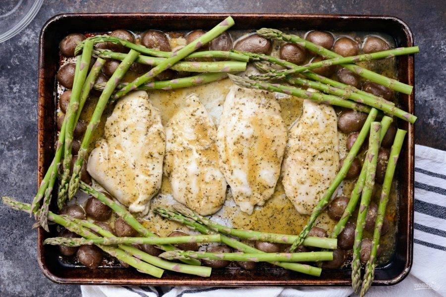 4. После этого вновь достаньте противень. Добавьте на него спаржу. Отправьте блюдо в духовку ещё на 10 минут.