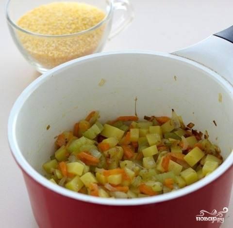 Картофель почистите от кожуры и промойте. Нарубите небольшиеми кубиками и бросьте в сотейник к овощам. Перемешайте ингредиенты, обжаривайте их еще пять минут. Высыпьте к овощам кукурузную крупу, залейте все водой. Варите до готовности, минут двадцать.
