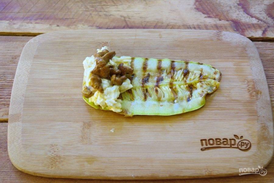 Один остывший кабачок выложите доску. На край кабачка уложите чайную ложку сырной начинки, добавьте немного маринованных лисичек. Сверните кабачковую пластинку рулетиком.