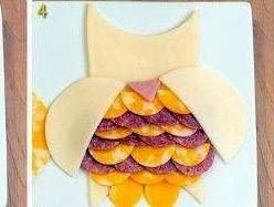Уложите чередуя колбаску и сыр, сделайте крылышки и носик.