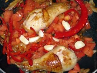 Добавьте к курице лук и перец, обжарьте до мягкости лука. Теперь можно добавить тертый чеснок, помидоры, специи и если надо, воду.