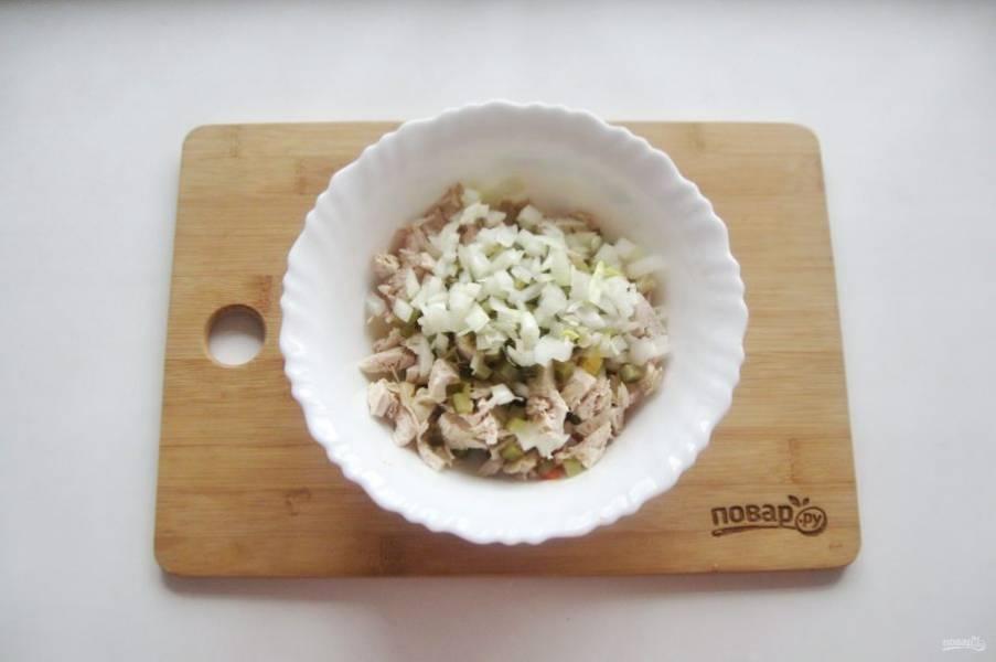 Репчатый лук очистите, помойте, мелко нарежьте. Выложите в мисочку и обдайте кипятком. Через 5 минут воду слейте, а лук добавьте в салат.