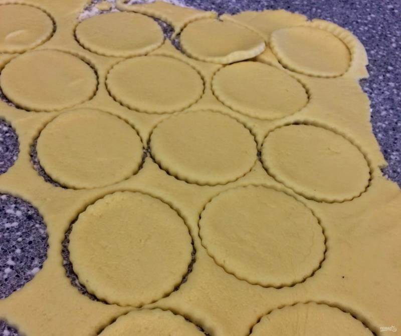 1.В чашу миксера выложите сливочное масло и творог, хорошенько разомните все в однородную массу. Добавьте муку и разрыхлитель, замесите тесто и отправьте его в холодильник на несколько часов. Достаньте охлажденное тесто и раскатайте тонко, вырежьте кружочки.