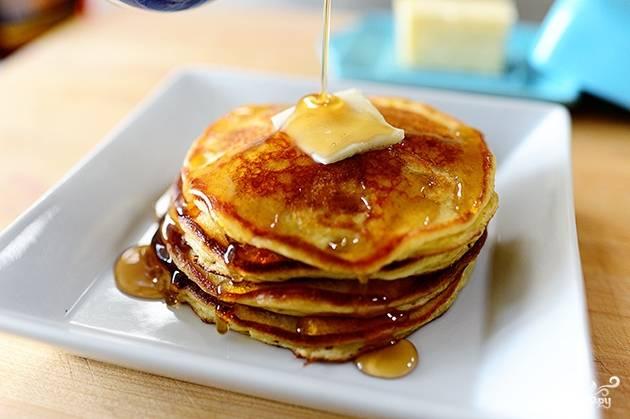 11. Выкладывайте следующие оладьи, чередуя их с маслом. А после полейте сверху медом, сгущенкой или любимым сиропом. Просто пальчики оближешь!