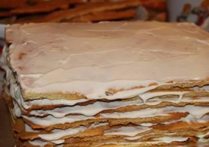 Обрезаем по бокам коржи, чтобы придать им прямоугольную форму. Обрезки коржей измельчаем в крошку. Часть крошки смешиваем со сметаной и промазываем бока торта. Сам торт формируем из коржей, смазанных кремом.
