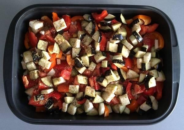 Все остальные овощи нарезаем кубиками одинаковой величины. Укладываем поверх картофеля все порезанные овощи и присыпаем специями для овощей и солью.
