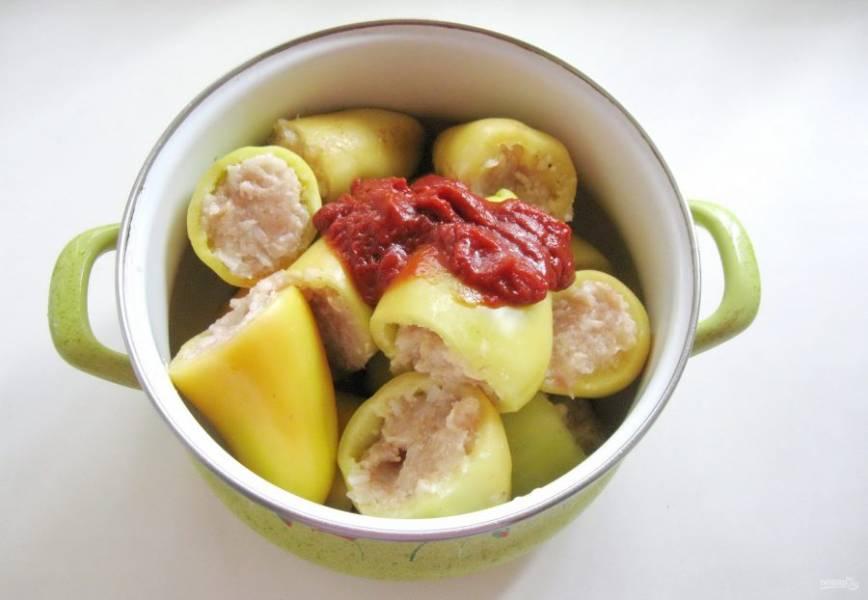 Добавьте томатную пасту, налейте воду так, чтобы она доходила до середины перцев. В процессе тушения перцы выделят очень много сока.