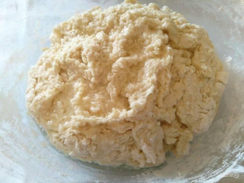 Добавьте соль и постепенно всыпьте просеянную муку, размешивая тесто ложкой. Как только оно начнёт собираться в комок, влейте подсолнечное масло.