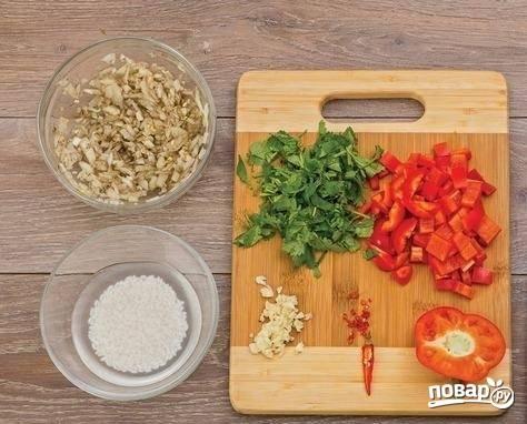 2. Когда мясо готово, можно заняться овощами. Очистите и измельчите лук, чеснок и перец. Вымойте и обсушите немного кинзы. Рис залейте водой минут на 5, а после обсушите.