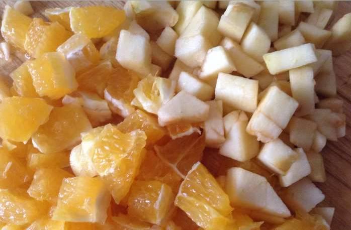 1. Нарезаем апельсин и яблоко крупными кусочками. Виноградинки и маслины делим пополам. Орехи измельчим и посыпаем салат.