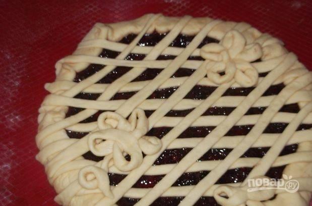 При помощи полосок теста украсьте пирог с вареньем в виде сетки. Также сделайте красивые цветы или листики. Смажьте взбитым яйцом. Поставьте пирог в духовку и выпекайте при температуре сто восемьдесят градусов полчаса.