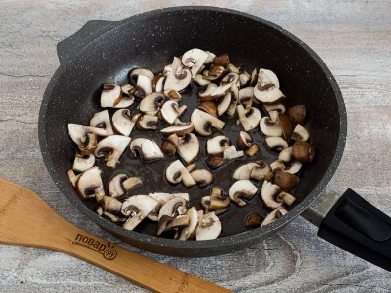 В сковороде с толстым дном или в казане нагрейте немного масла и обжарьте нарезанные  пластинами грибы. Затем жареные грибы уберите из сковороды на тарелочку.