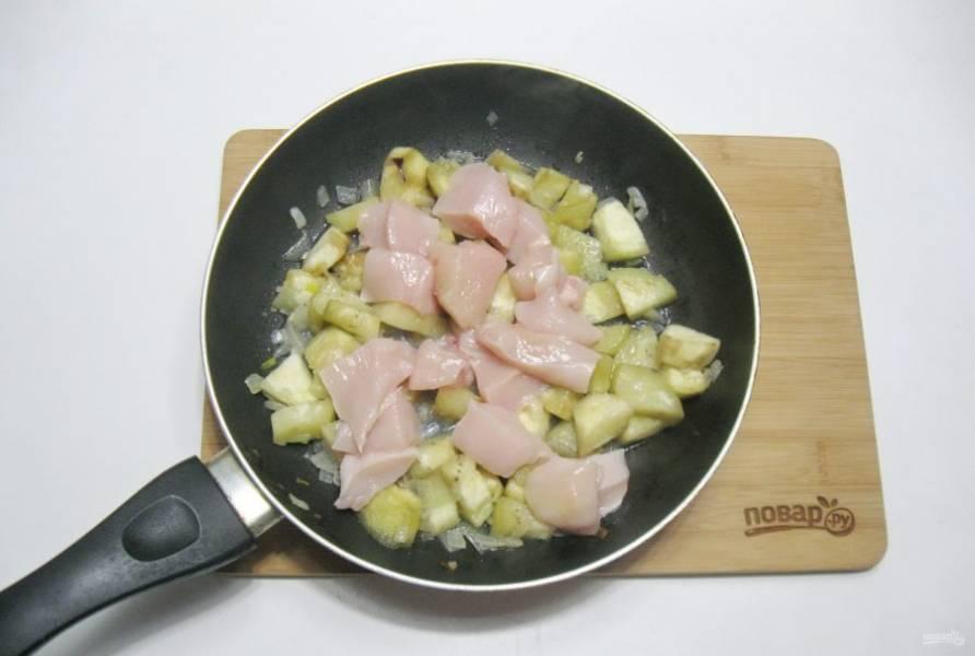 Куриное филе помойте, нарежьте кусочками и добавьте к луку и баклажану.