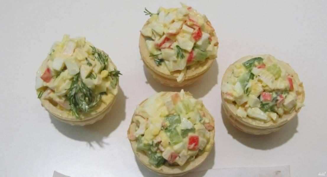 5. Теперь вы знаете, как приготовить тарталетки с крабовыми палочками и огурцом. Подавать их можно на большом блюде с листьями салата и зеленью.
