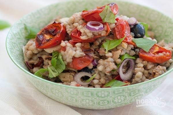 В холодную гречку добавьте нарезанные маслины, отжатый репчатый лук, остывшие помидоры-конфи и кусочки филе консервированной скумбрии. Добавьте листья базилика, полейте салат оливковым маслом. Перемешайте, попробуйте и при необходимости добавьте соль. Дайте салату настояться несколько часов, а затем подавайте на стол.