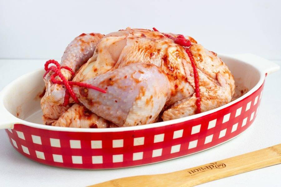 Свяжите кулинарной или силиконовой нитью ножки и крылышки. Поставьте запекаться в разогретую до 200 градусов духовку на 40-45 минут, затем полейте курицу выделившимся соком, накройте фольгой. Температуру убавьте до 150 градусов и запекайте ещё 40-50 минут.