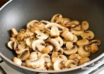 Готовый бекон переложите в тарелку. В сковороду налейте 2 столовые ложки растительного масла, выложите нарезанные грибы и обжарьте их до золотого цвета на среднем огне.
