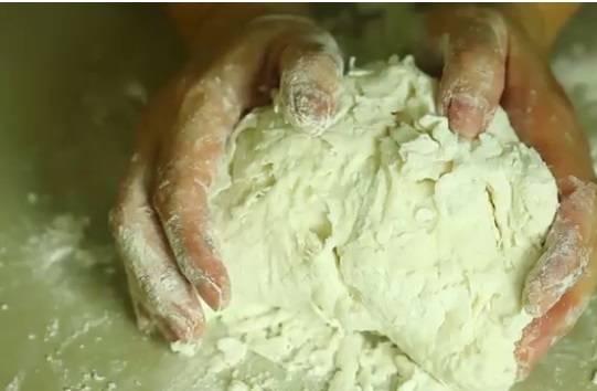 4. Когда тесто станет густеть, выложить его на присыпанную мукой поверхность и продолжать вымешивать руками. Оно должно быть мягким, эластичным и, конечно же, без комков.