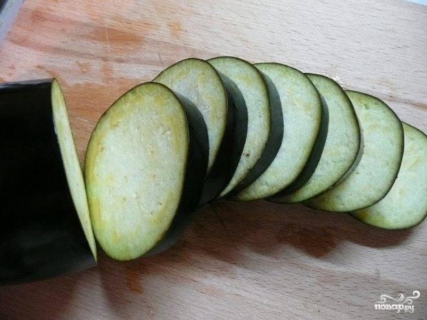Баклажаны моем и нарезаем кружочками толщиной примерно 0.5 сантиметра. Для того, чтобы удалить горечь, замачиваем нарезанные баклажаны в соленой воде примерно на 30 минут.