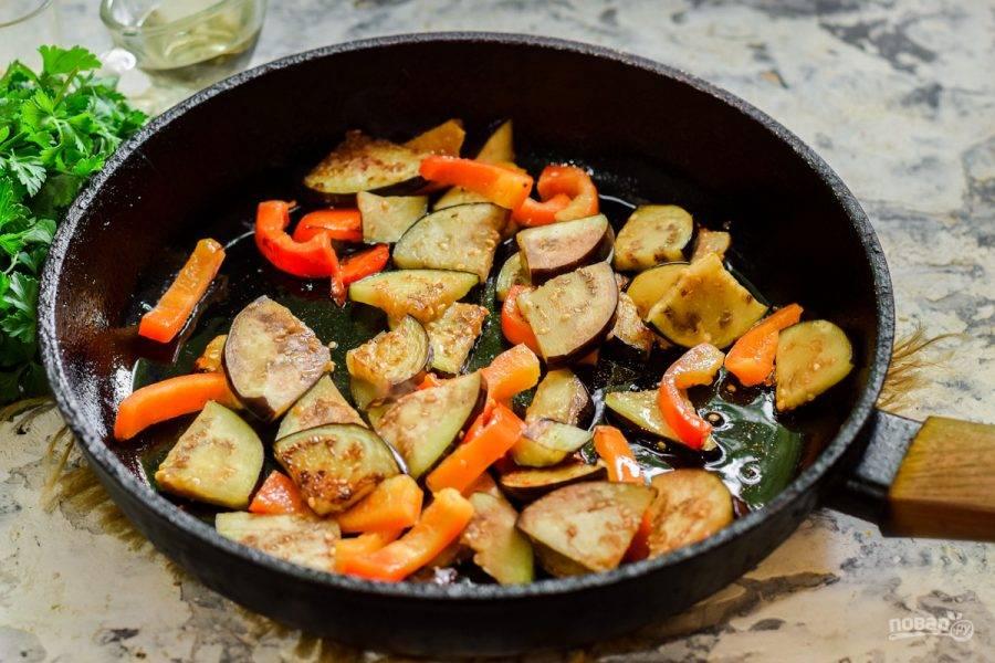 В сковороде разогрейте растительное масло, выложите баклажаны и перец. Жарьте 5-7 минут на небольшом огне до готовности.