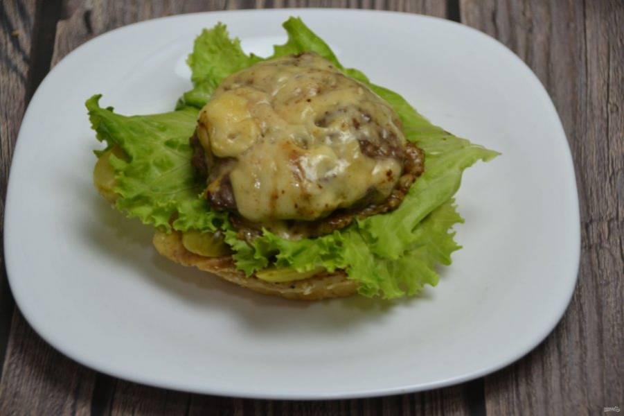 На салатные листья выложите котлету в сыре.