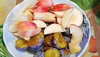Подготовим начинку. Промойте яблоки и сливы. Яблоки порежьте дольками, сливы разделите пополам, а косточки удалите.