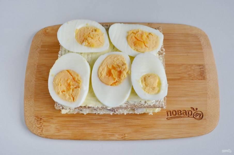 Накройте селедку кусочком серого хлеба, смажьте его маслом и положите сверху колечки вареного яйца.