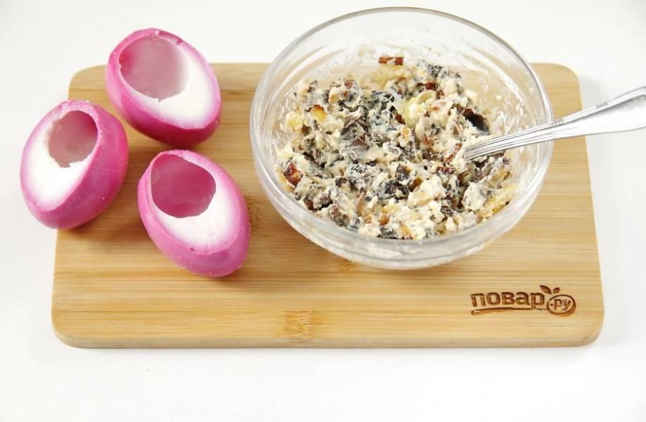 Добавьте к начинке майонез, соль и перец по вкусу. Перемешайте, растирая желтки до однородного состояния.