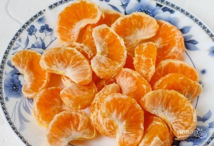 Очистите дольки сладких мандаринов от кожуры и белых волокон. Обваляйте дольки мандаринов в муке, чтобы в процессе запекания они не упали на дно формы.