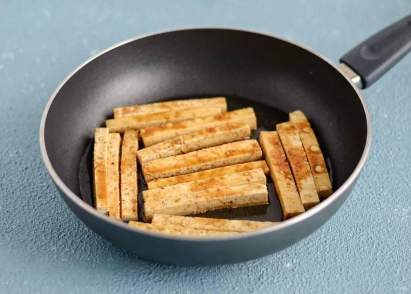 Тофу нарежьте брусочками, добавьте сухой чеснок и соевый соус. Обжарьте тофу со всех сторон на среднем огне до золотистой корочки.