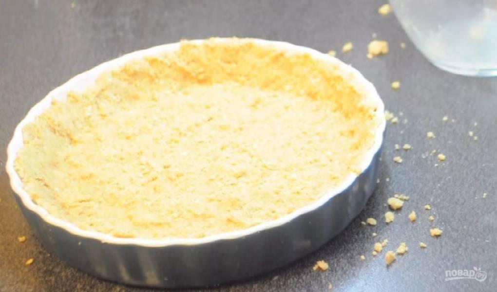 2. Равномерно распределите песочную основу по дну и бортикам формы, в которой будете выпекать чизкейк.