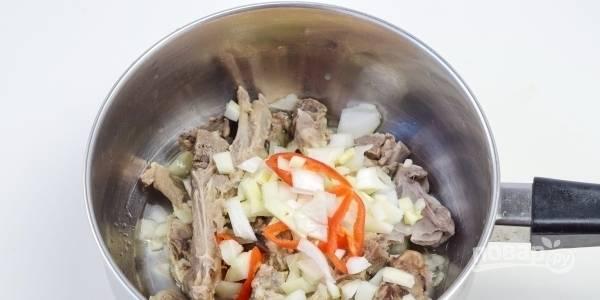 В сотейник влейте растительное масло и разогрейте его на плите. Затем вымойте и нарежьте бараньи ребрышки. Обжарьте их на масле до румяной корочки. Добавьте подготовленные овощи и обжаривайте еще пять минут.