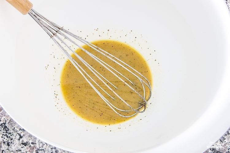 6. Для приготовления заправки соедините в отдельной мисочке оливковое масло, уксус, мед, горчицу, молотый чеснок, соль и перец. Взбейте все до однородности.
