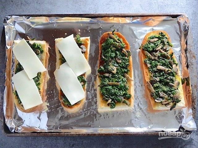 4.Достаньте хлеб и распределите приготовленную начинку. Уложите поверх начинки сыр.