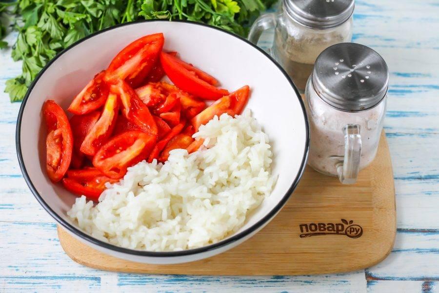Помидоры промойте в воде, вырежьте из плодов зеленые черенки, нарежьте мякоть ломтиками в салатник или глубокую емкость. Выложите туда же чуть остывший рис.