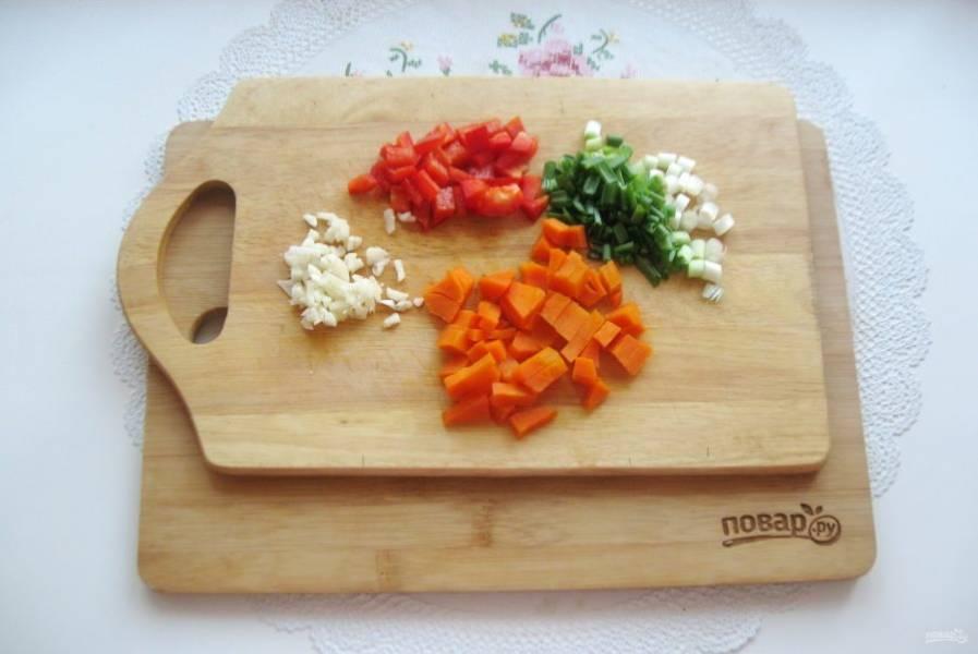 Мелко нарежьте зеленый лук, морковь, болгарский перец и чеснок.