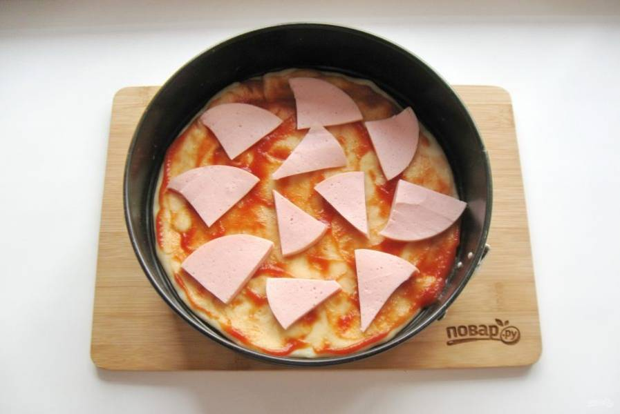 Вареную колбасу нарежьте и выложите на тесто.