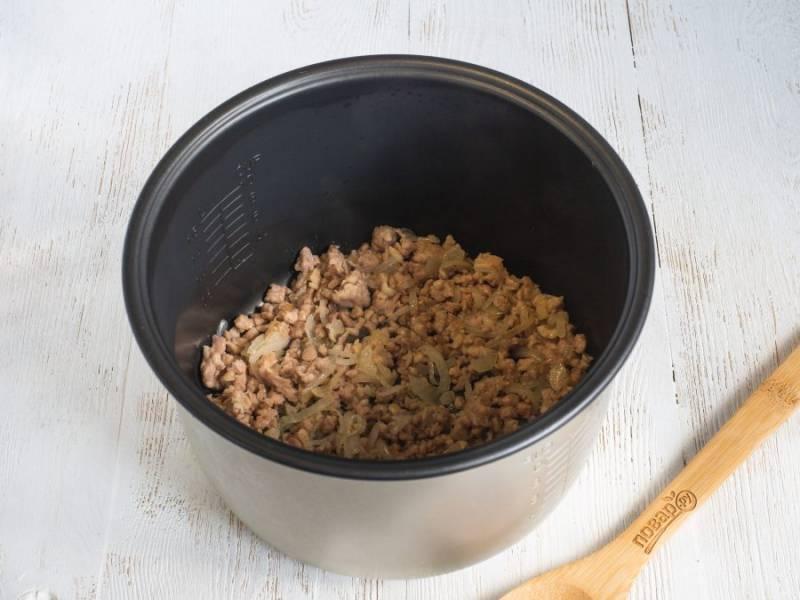 """Лук нарежьте полукольцами или мельче, обжарьте в растительном масле на сковороде или сразу в чаше мультиварки на режиме """"жарка"""" или """"выпечка"""". Когда лук будет прозрачным, добавьте фарш и рубленный чеснок. Посолите по вкусу и жарьте до готовности фарша. Жидкость лучше всю выпарить. Это будет первый слой запеканки."""