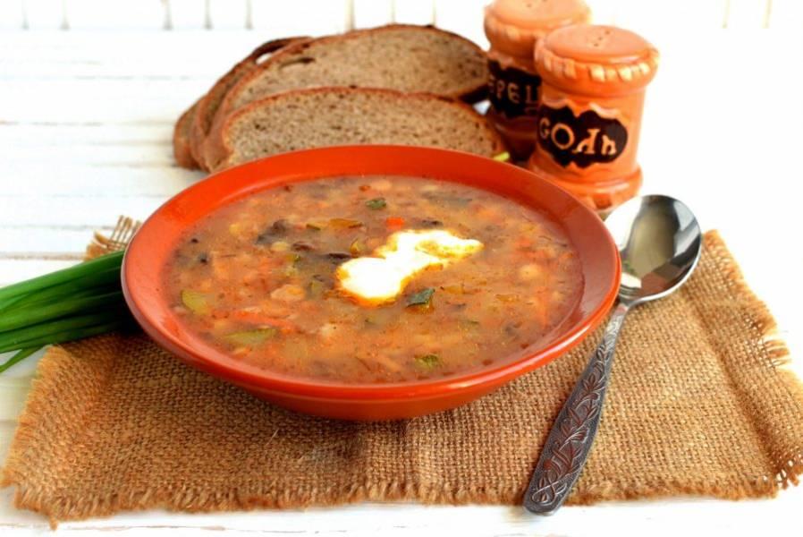 Подавайте рассольник со свежей зеленью и мягким ржаным хлебом, добавив в тарелки сметану.