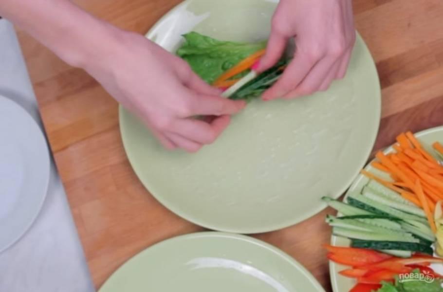 3. Затем лист рисовой бумаги окуните с обеих сторон в холодную воду и соберите ролл: на рисовую бумагу положите креветки, листья салата, нарезанные соломкой овощи и манго, кинзу. Затем аккуратно сверните ролл.