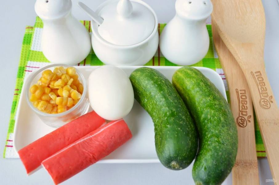 Подготовьте продукты: вымойте огурцы, разверните крабовые палочки, отварите яйцо и очистите его от скорлупы.