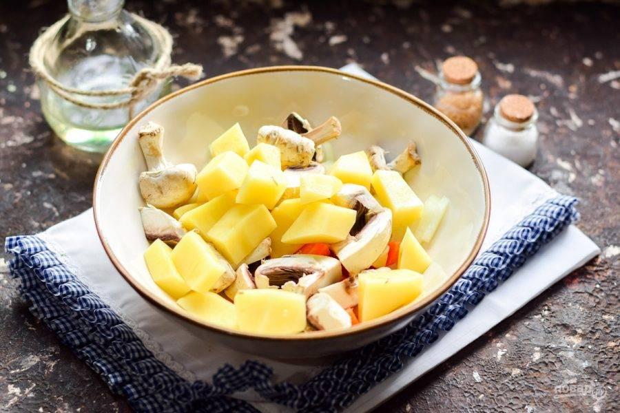 Очистите клубни картофеля, сполосните и просушите. Нарежьте картофель крупными брусками и добавьте к овощам.