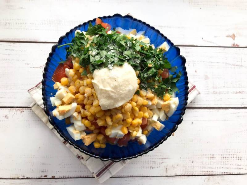 Высыпьте консервированную кукурузу, добавьте майонез, мелко нарезанную зелень, соль и хорошо все перемешайте.