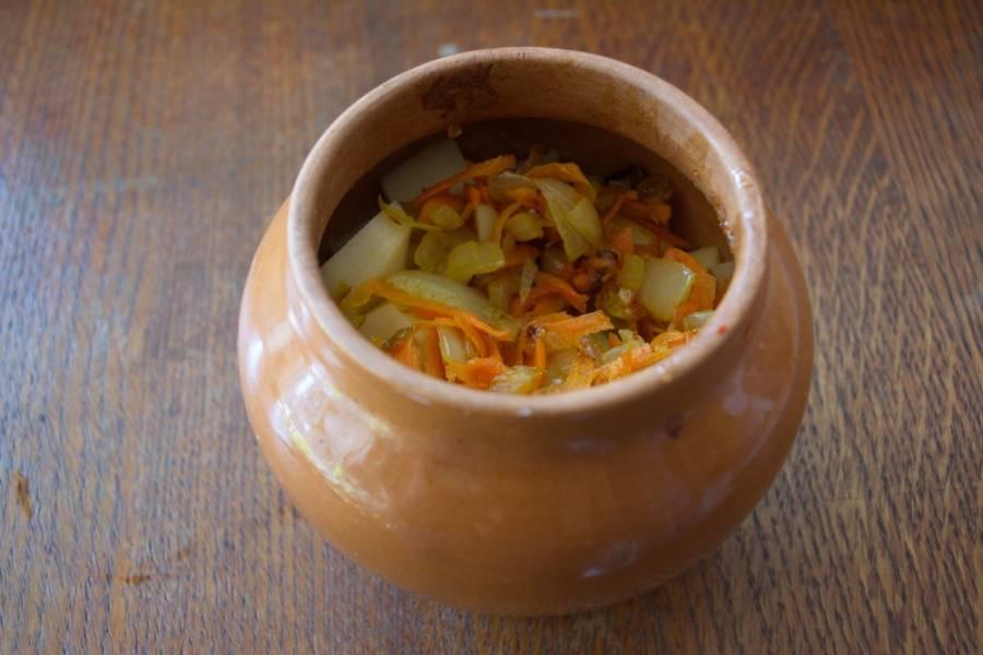 На растительном масле обжарьте нарезанный репчатый лук и морковь. Зажарку выложите в горшочки.