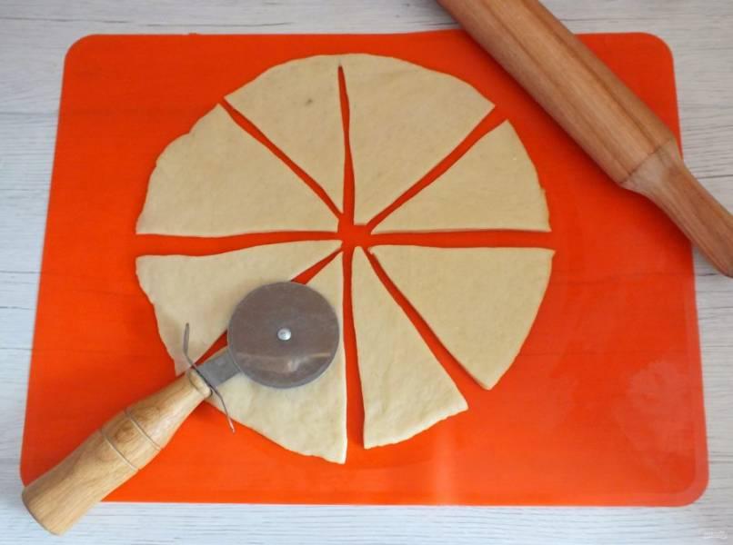 Раскатайте одну часть в пласт толщиной 0,3-0,5 см. Разрежьте на 8 секторов.
