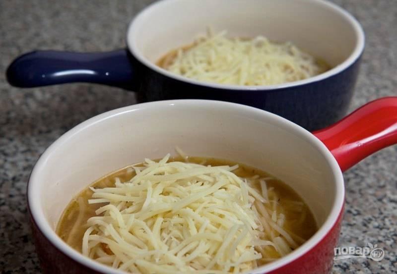 Разлейте суп по порционным жаропрочным тарелкам, опустите в каждую обжаренный ломтик хлеба, а сверху присыпьте тертым сыром.