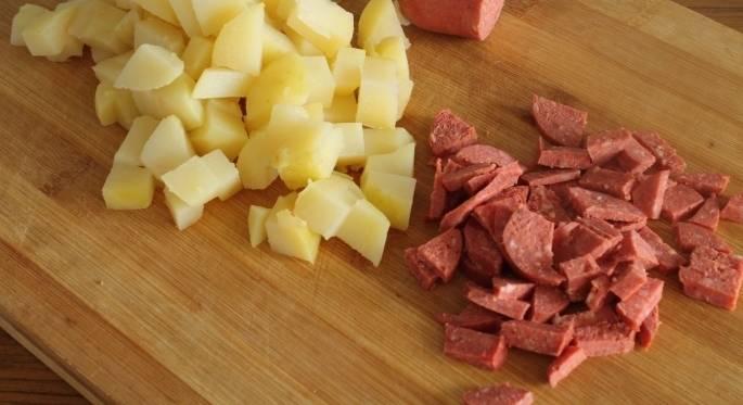 2. Делаем все поочередно: сразу нарезаем картофель и колбасу кубиками среднего размера.